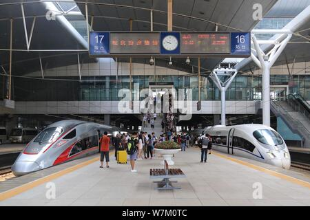 A 'Fuxing' high-speed bullet train on the Beijing-Tianjin Intercity Railway, left, and a CRH (China Railway High-speed) bullet train are pictured at t - Stock Photo