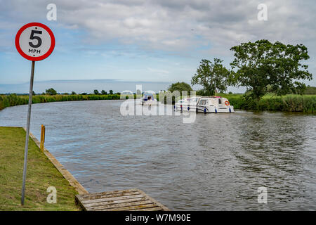 A 5mph speed limit sign on the bank of the River Bure in Horning. Speed limit signs are prevalent along the rivers of the Norfolk Broads, and whilst c - Stock Photo