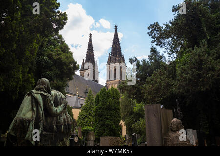 Tombstones and statues at the Vysehrad cemetery and Basilica of Saints Peter and Paul on the grounds of Vysehrad Castle in Prague, Czech Republic. - Stock Photo
