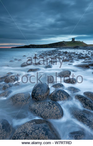 Dunstanburgh Castle at dawn from Embleton Bay, Northumberland, England. April 2013. - Stock Photo