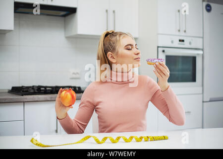 Dieting concept. Young Woman choosing between Fruits and Sweets - Stock Photo