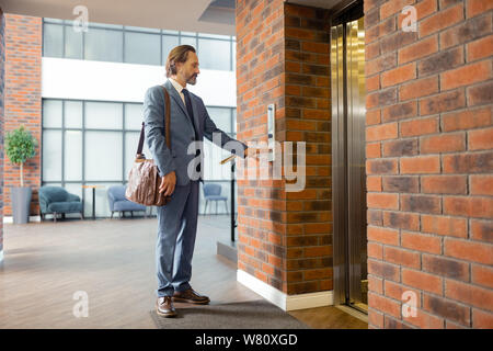 Stylish businessman leaving business center in the evening - Stock Photo