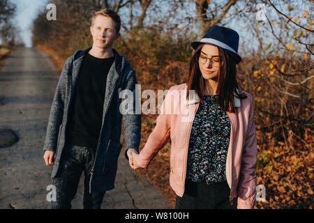 Lovely young couple walking while dating by holding hand while girl is looking down and man is looking away outside. - Stock Photo