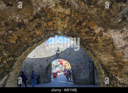 View of Tenby town centre through Five Arches Gate in its historic medieval city walls, a walled seaside resort in Pembrokeshire, south Wales coast - Stock Photo