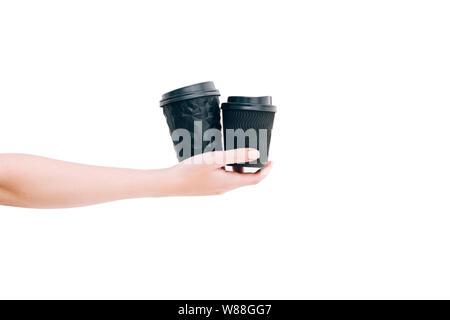 Two black paper coffee cups to go in woman's hand isolated on white. Mockup. - Stock Photo