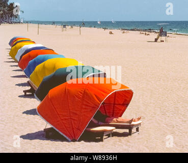 A vacationer who wants to get a suntan on his legs sticks them out from the canopy of a bright orange beach cabana on the wide sandy beach along the Atlantic Ocean at Fort Lauderdale, Florida, USA. These colorful cabanas, which can be rented by the hour or the day, provide shade and some privacy to beachgoers at this popular holiday destination on the southeast coast of the Sunshine State. - Stock Photo