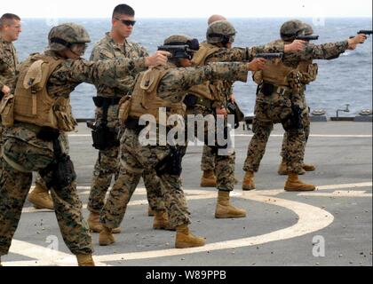U.S. Marines assigned to the 2nd Fleet Antiterrorism Security Team Company, 3rd Platoon, fire 9mm pistols at targets during small-arms weapons familiarization training aboard the USS Blue Ridge (LCC 19) on March 26, 2005, underway in the South China Sea. - Stock Photo