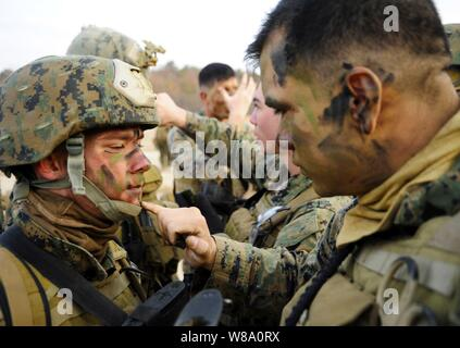 Cpl. Mario Melendez (right), assigned to 2nd Platoon, Company Pacific, Fleet Anti-Terrorism Security Team applies camouflage paint to Lance Cpl. Tyler Courtney before a tactical movement exercise at Camp Rodriguez, Republic of Korea, on March 3, 2012.   Approximately 50 Marines conducted training at the Camp Rodriguez Live Fire Complex. - Stock Photo