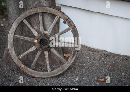 An old wooden cartwheel stands at the wall of the house - Stock Photo
