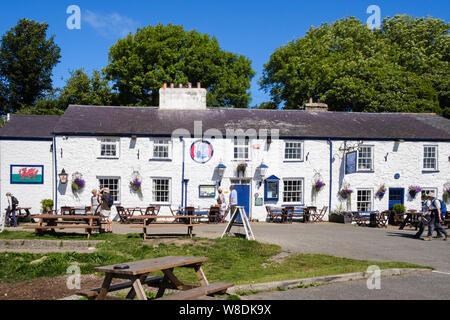 The historic Ship Inn pub with outdoor tables in front. Red Wharf Bay (Traeth Coch), Isle of Anglesey, Wales, UK, Britain - Stock Photo