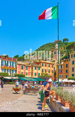 Portofino, Italy - July 1, 2019: Italian flag on the tall flagpole and waterfront with walking people in Portofino - famous resort on the Italian rivi - Stock Photo