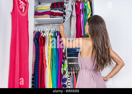 Home woman choosing her fashion outfit in dressing room. Woman in bedroom walk-in organized closet looking at clothes hanging deciding what shirt to wear in the morning. Shopping store clothing rack. - Stock Photo