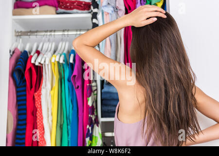 Home closet indecision woman choosing her fashion outfit on clothing rack. Shopping spring cleaning concept. Morning woman having too many clothes thinking of what to wear in organized clean walk-in. - Stock Photo