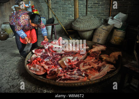 A Chinese villager picks meat from a butchered pig before hanging is up on the ceiling at home in preparation for the upcoming Chinese Lunar New Year, - Stock Photo