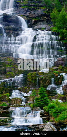 Vertical hires panorama of a waterfall streaming over rocks with trees and vegetation, Norway - Stock Photo