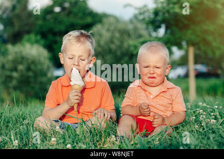 Two Caucasian funny children boys siblings sitting together eating sharing one ice-cream. Toddler younger baby crying and older brother teasing him. L - Stock Photo