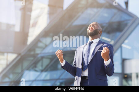 Afro businessman shaking fists rejoicing success in urban area - Stock Photo