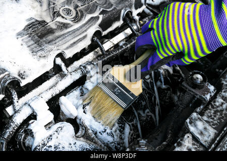 A man cleaning car engine with shampoo and brush. Car detailing or valeting concept. Selective focus. Car detailing. Cleaning with sponge. Worker clea - Stock Photo