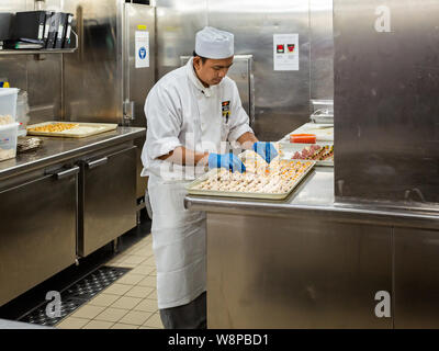 Behind the scenes view of food preparation in the kitchen, galley on board a large cruise ship at Sea in Queen Victoria in the Baltic Sea on 24 July 2 - Stock Photo