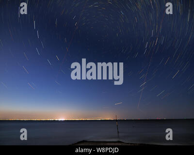 Sheerness, Kent, UK. 10th August, 2019. UK Weather: a clear evening in Sheerness, Kent. Pictured: star trails show the rotation of the Earth in this 25 minute in-camera composite long exposure image. The red straight lines crossing the image are light trails from planes flying to or from Southend on Sea airport. Credit: James Bell/Alamy Live News - Stock Photo