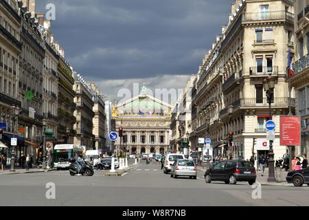 Paris/France - August 19, 2014: View to the Opera de Paris at the end of the Avenue de l'Opera illuminated by the sun before the storm. - Stock Photo