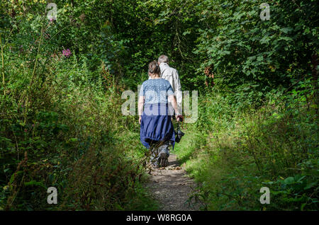 A couple on a walk down a trail through woods in the South Staffordshire countryside. - Stock Photo