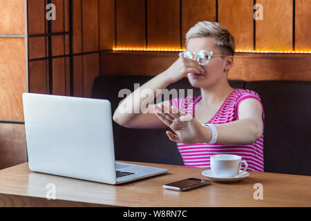 bad smell. Portrait of unhappy confused young woman with short hair in pink t-shirt and eyeglasses is sitting in cafe, covering nose with finger and p - Stock Photo