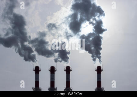 Silhouettes of pipes emitting dark steam into the atmosphere. Steam smoke smog swirling from industrial pipes. Atmospheric air pollution, environmenta - Stock Photo