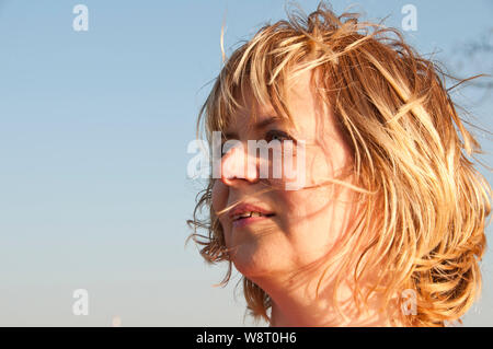 portrait of an optimistic blonde woman in her forties - Stock Photo