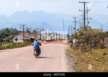 Driving thru laotian village and scenic hills in the horizon - Stock Photo