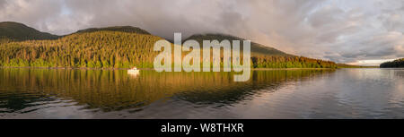 Motorboat Moored in Calm Water in the Evening at Cleveland Passage Between Whitney Island  and the Fanshaw Range on Mainland North America, Alaska USA - Stock Photo