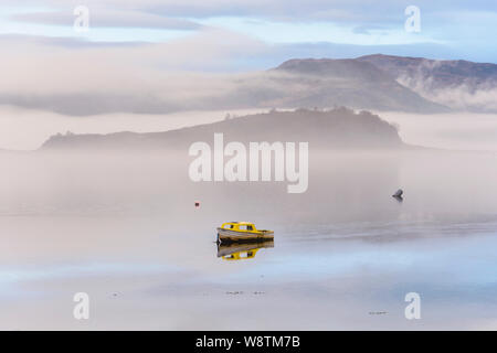 Small boat in mist and fog on Loch Carron, Wester Ross, Highlands of Scotland - Stock Photo