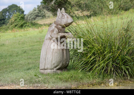 Giant carved wooden squirrel sitting in grass field, Cotswolds, UK - Stock Photo
