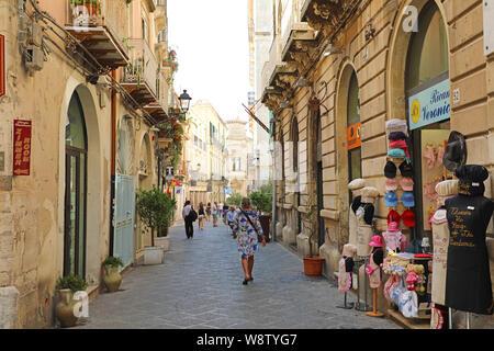 SYRACUSE, ITALY - JUNE 22, 2019: Narrow beautiful street in the island Ortigia, Syracuse, Sicily, Italy - Stock Photo