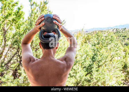 Back of young fit shirtless man with heavy kettlebell doing triceps exercise and muscles in outdoors outside park holding weight lifting - Stock Photo