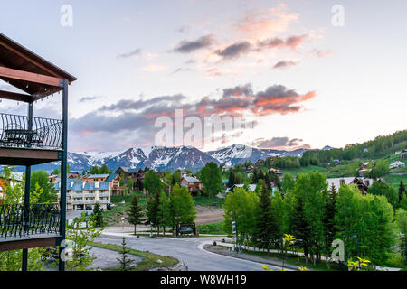 Mount Crested Butte, USA - June 21, 2019: Colorado village in summer with sunrise by apartment houses on hills with green trees and gothic road - Stock Photo