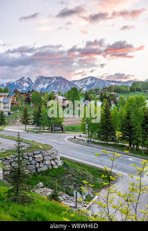 Mount Crested Butte, USA - June 21, 2019: Colorado village sign in summer with sunrise and houses on hills with green trees and gothic road - Stock Photo