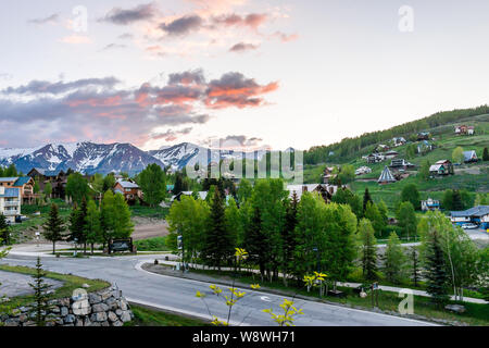 Mount Crested Butte, USA - June 21, 2019: Colorado village in summer with colorful sunrise by houses on hills with green trees and main road - Stock Photo