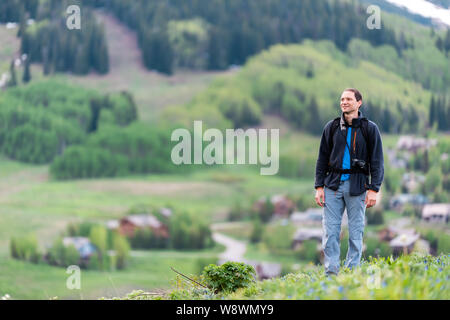 Man happy hiking on Snodgrass trail with bokeh background view of Mount Crested Butte, Colorado peak and village in summer - Stock Photo