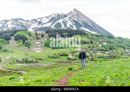Man hiking on Snodgrass trail with view of Mount Crested Butte, Colorado peak and ski village in summer - Stock Photo