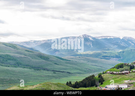 Mount Crested Butte, USA - June 21, 2019: Colorado alpine meadows and houses on Snodgrass hiking trail in summer on cloudy day with green grass and mo - Stock Photo