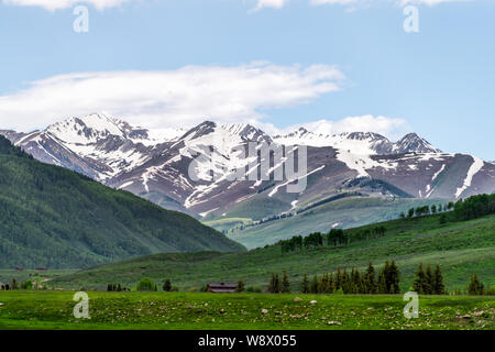 Mount Crested Butte village in summer with green grass and snow mountains with alpine meadows in early summer - Stock Photo