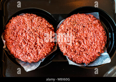 Flat top closeup of two raw uncooked red vegan plant based meat burger patties in packaging - Stock Photo