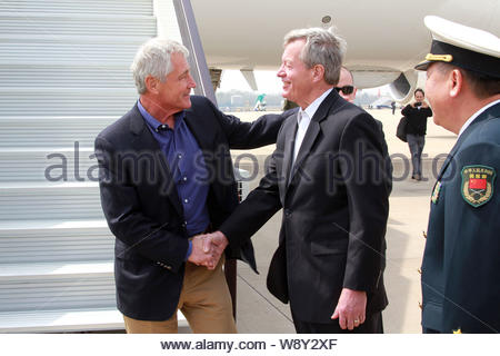 U.S. Secretary of Defense Chuck Hagel, left, shakes hands with U.S. Ambassador to China Max Baucus, center, upon his arrivial at the Qingdao Liuting I - Stock Photo