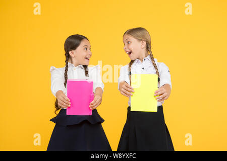 Study together. Kids cute students. Schoolgirls best friends excellent pupils. School friendship. Schoolgirls wear school uniform. Knowledge day. School day. Girl with copy books or workbooks. - Stock Photo