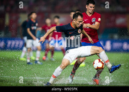English-born Taiwanese football player Tim Chow, right, of Henan Jianye challenges a player of Beijing Renhe in their 23rd round match during the 2019 Chinese Football Association Super League (CSL) in Zhengzhou city, central China's Henan province, 9 August 2019. Henan Jianye defeated Beijing Renhe 2-1. - Stock Photo