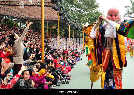 Visitors watch traditional performance during the Spring Festival vacation in Splendid China Folk Culture Village in Shenzhen city, south Chinas Guang - Stock Photo