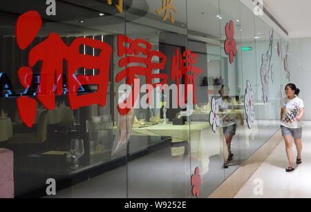 --FILE--A pedestrian walks past a Xiang E Qing restaurant in Beijing, China, 17 July 2013.   Chinas high-end restaurants have gone into crisis under P - Stock Photo