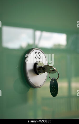 Key on a deposit box with the number 33 - Stock Photo