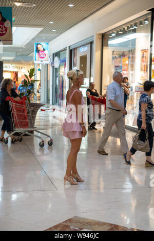 Lady looking at the shops in a busy shopping mall in France - Stock Photo